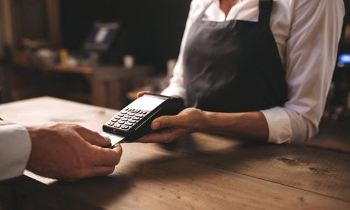 Closeup of a customer inserting their credit card into a payment device