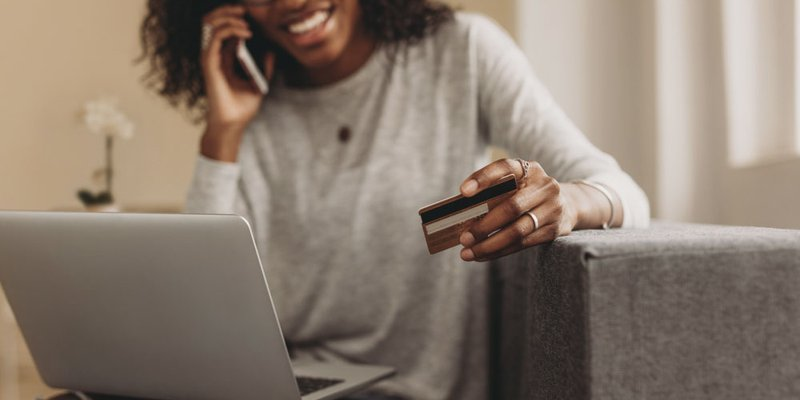 A woman gives her credit card info to someone over the phone