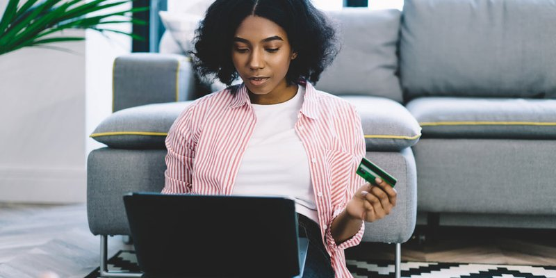 A woman purchases something on her laptop via credit card in her modern living room