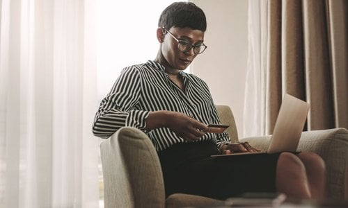 A woman pays for something via credit card on her laptop
