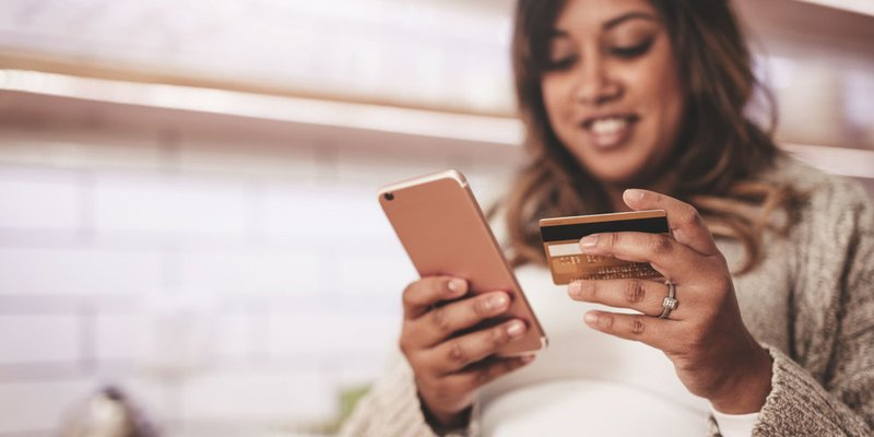 A pregnant woman types her credit card into into her phone