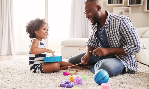 A dad plays with some toys with his toddler daughter on their living room carpet