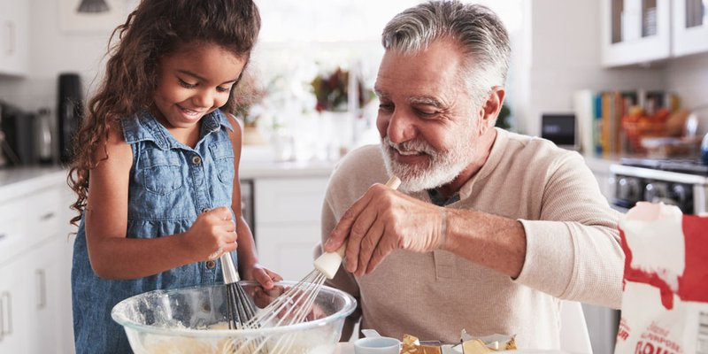 A grandpa bakes with his granddaughter in a bright sunny kitchen