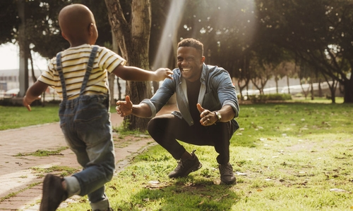 A young son runs towards his happy dad with open arms outside in a park