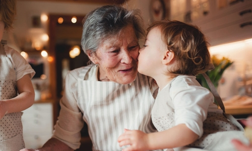A toddler kisses their grandma in this cute portrait taken at home