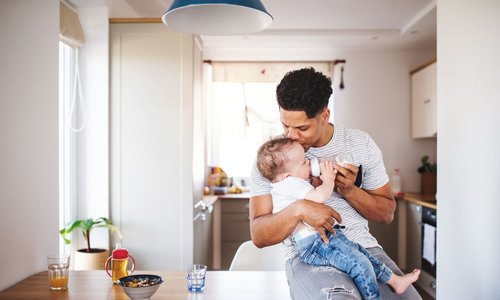 A son kisses his toddler on the head in their bright sunny home