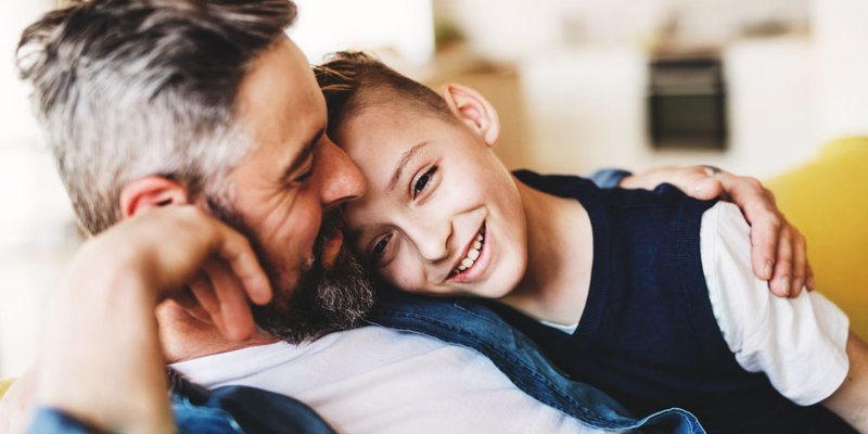 A son snuggles into his dad on the couch at home