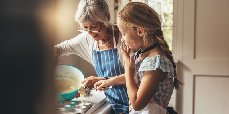 A grandma and her granddaughter bake in the kitchen