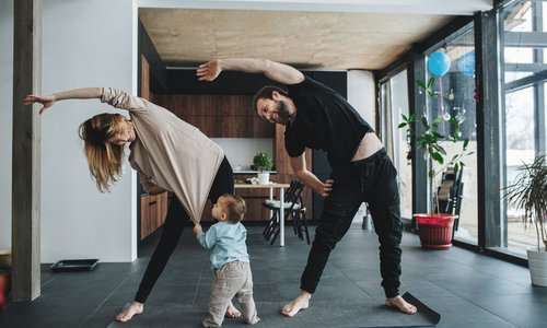 A mom and dad do stretches at home in their condo while their little baby tugs on mom's shirt