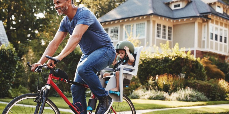 A dad bikes through his neighbourhood with his child in a bike seat behind him