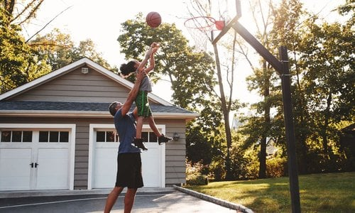 A dad picks up his daughter and holds her up high so she can score a basket at their driveway basketball hoop