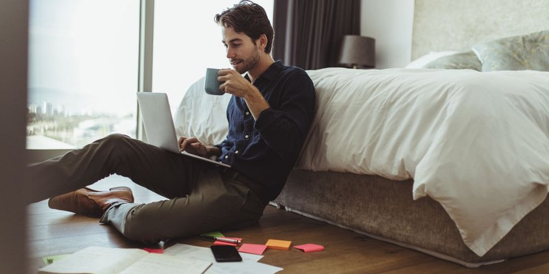 A man sits on his bedroom floor drinking a coffee with lots of paperwork and ideas surrounding him