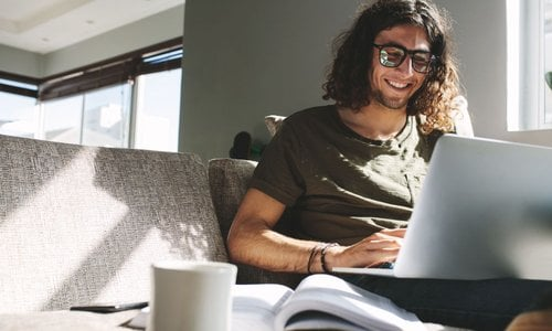 Millennial man wearing big trendy glasses works on his laptop while sitting on modern sofa