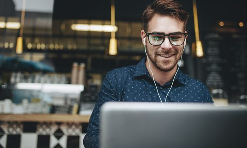 Millennial man with white earbuds in works on his laptop in downtown coffee shop