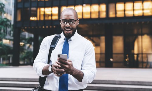 Professional man with blue tie stands outside his downtown office space and looks at his mobile phone