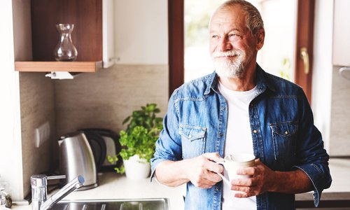 A hip senior man in a denim shirt looks out his kitchen window
