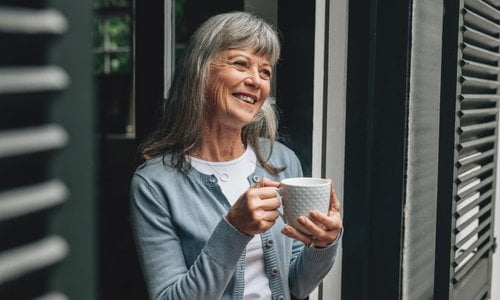 A senior woman enjoys a cup of coffee while standing outside on her porch