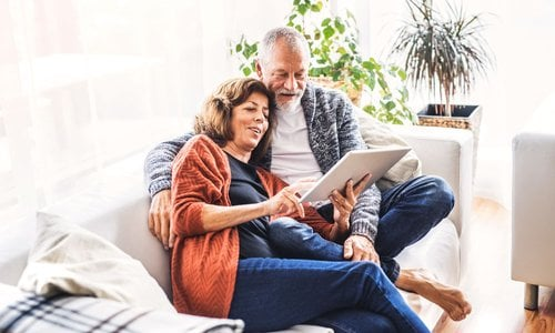 A couple relaxes together on the couch while looking at their tablet