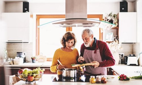 An older couple stirs a pot of sauce while cooking together in their bright modern kitchen
