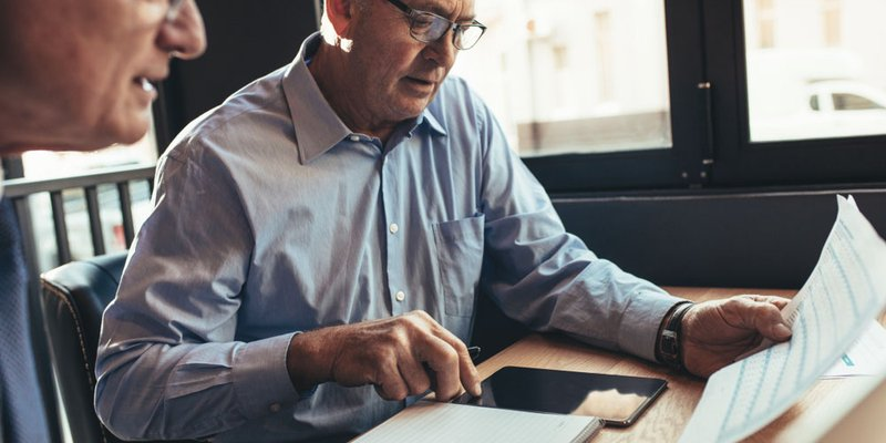 Older professional men working together at a desk