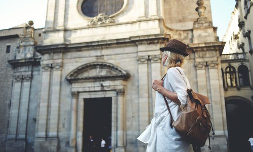 A stylish woman on vacation admires ancient archicture