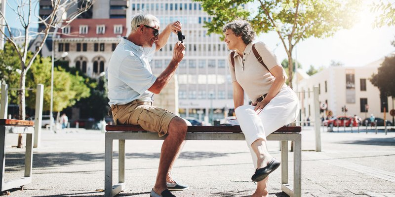 An older couple snaps photos of each other sitting outside on a park bench while travelling together