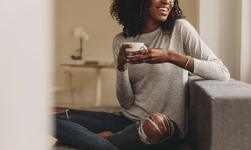 A young woman casually relaxes at home while sipping coffee and sitting on the floor