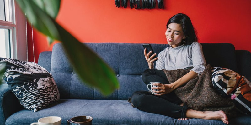A young woman sits on her couch, drinking a coffee and scrolling on her phone in bright, trendy downtown apartment