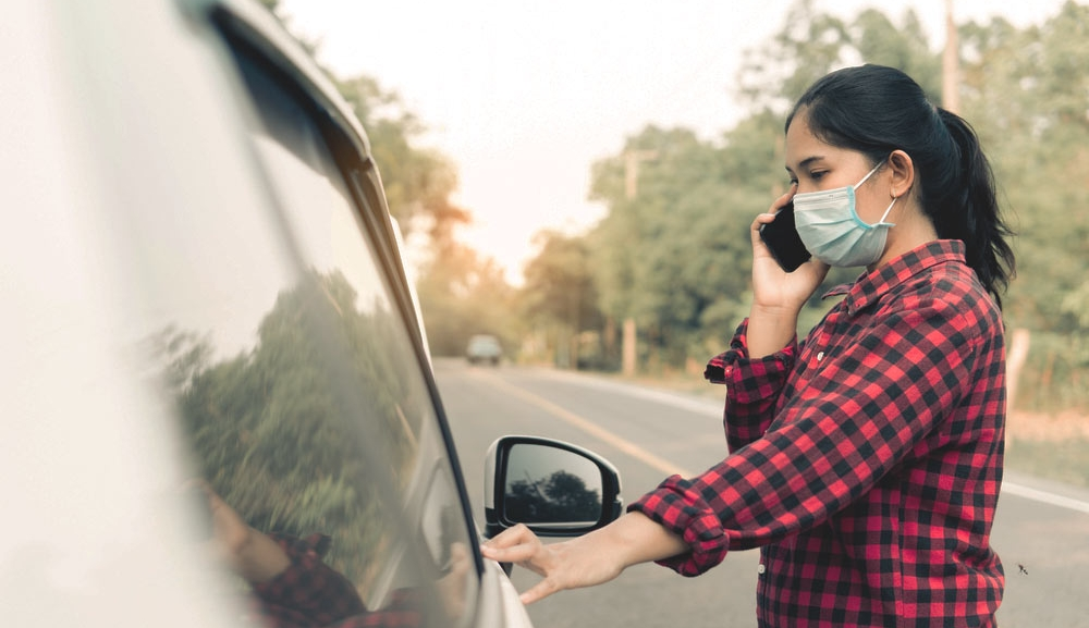 A woman with a face mask touches her vehicle while on the phone