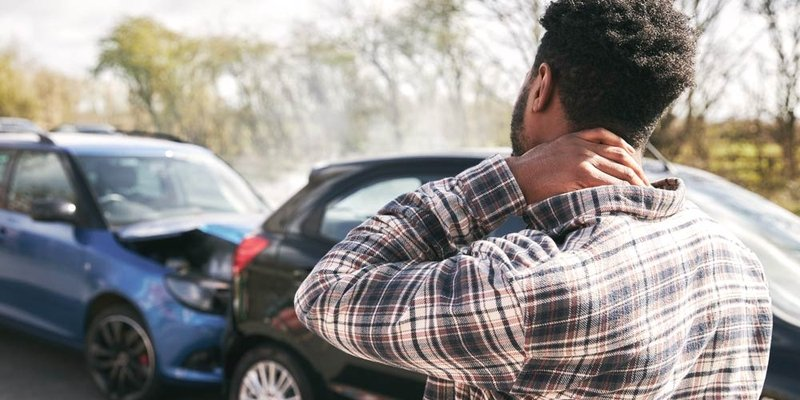 A man holds his neck after being involved in a rear-end collision/car accident