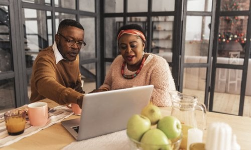 African American couple sitting at modern kitchen looking on their laptop