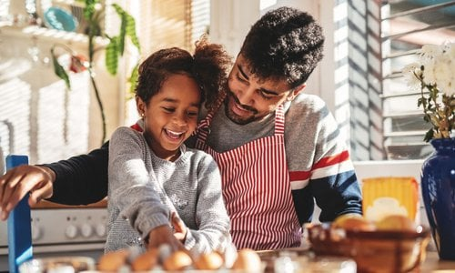 A father and child cracking eggs together in the kitchen