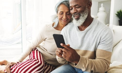 A senior couple snuggles on the couch while the man shows his wife something on his phone