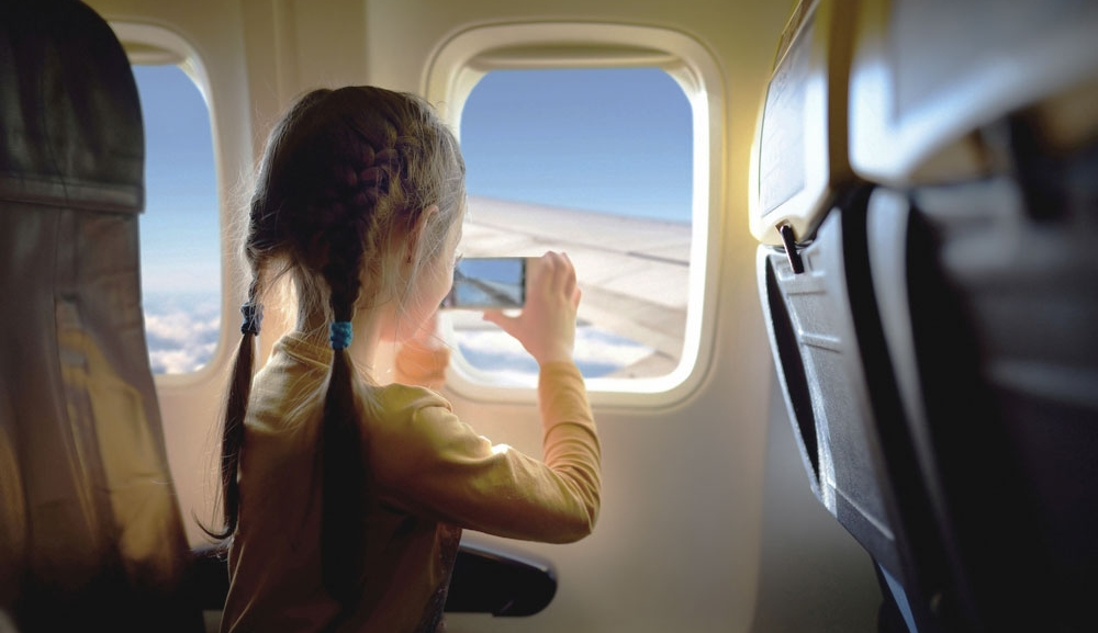 A young girl travelling on a plane takes a photo out the plane's window