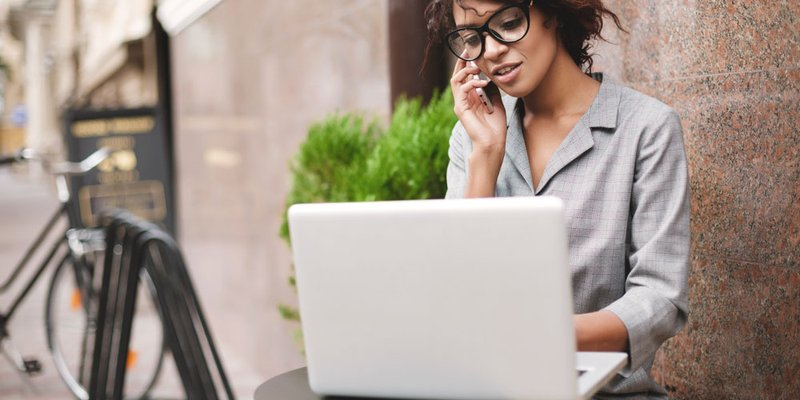 A professional woman in trendy glasses sits outside at a table while working on her laptop and talking on the phone