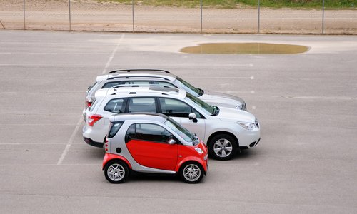 Three cars sizes small, medium and large are parked in a parking lot