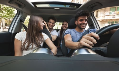 A driver sits happily behind the wheel with three passengers