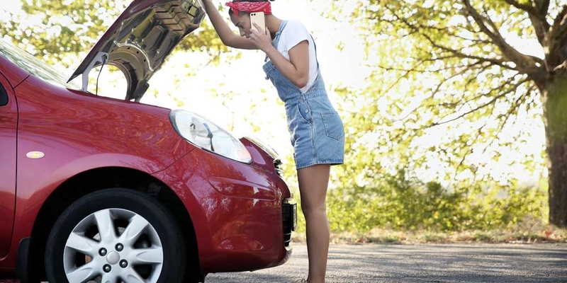 A woman looks under the hood of her car while on the phone