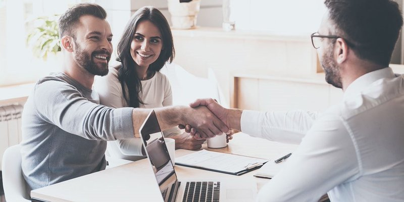 A young couple shakes hands with an advisor or broker at an office