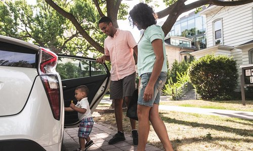 Young parents and their toddler son get ready to load into the car