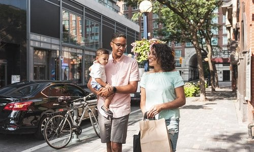 Young modern family with toddler son shopping in the city