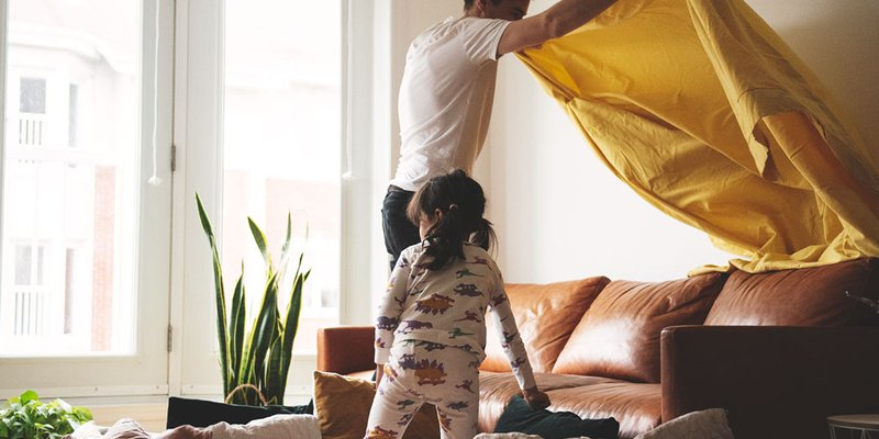 Father and toddler daughter use a yellow sheet to make a tent in bright sunny living room