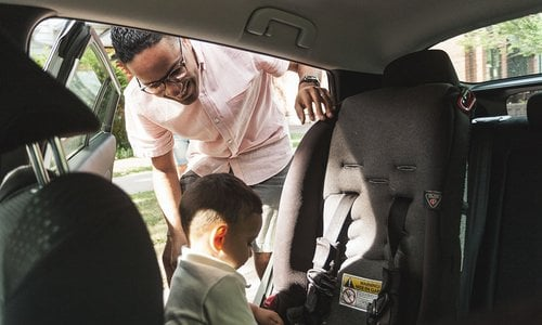 Dad gets his son ready in the back of the car while son plays with carseat