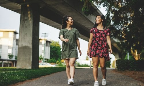 Two female friends walking downtown near the expressway