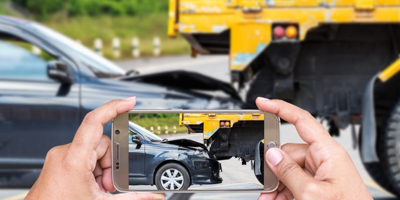 Person taking a photo on smartphone of minor car accident