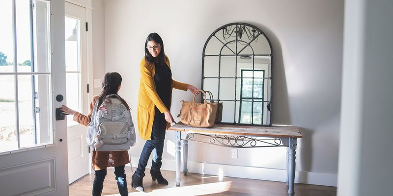 Mom and daughter entering their bright, modern home after a day of school and work