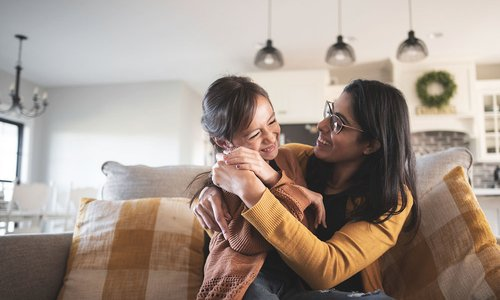 Mom snuggles her daughter on the couch in modern home