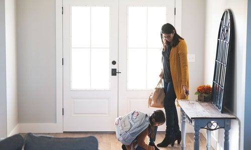 Mom and daughter getting ready to leave the house while daughter ties her shoes