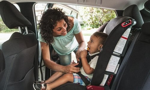 Mom buckles baby into the car seat in their family vehicle