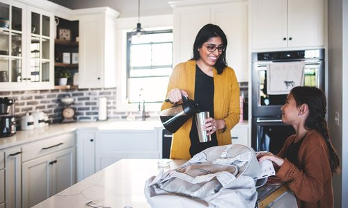 Mom pours herself a coffee while daughter packs her school bag in the morning